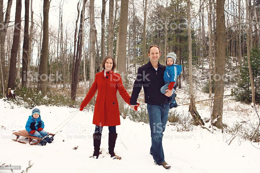 Family Walking Through Woods in Winter stock photo