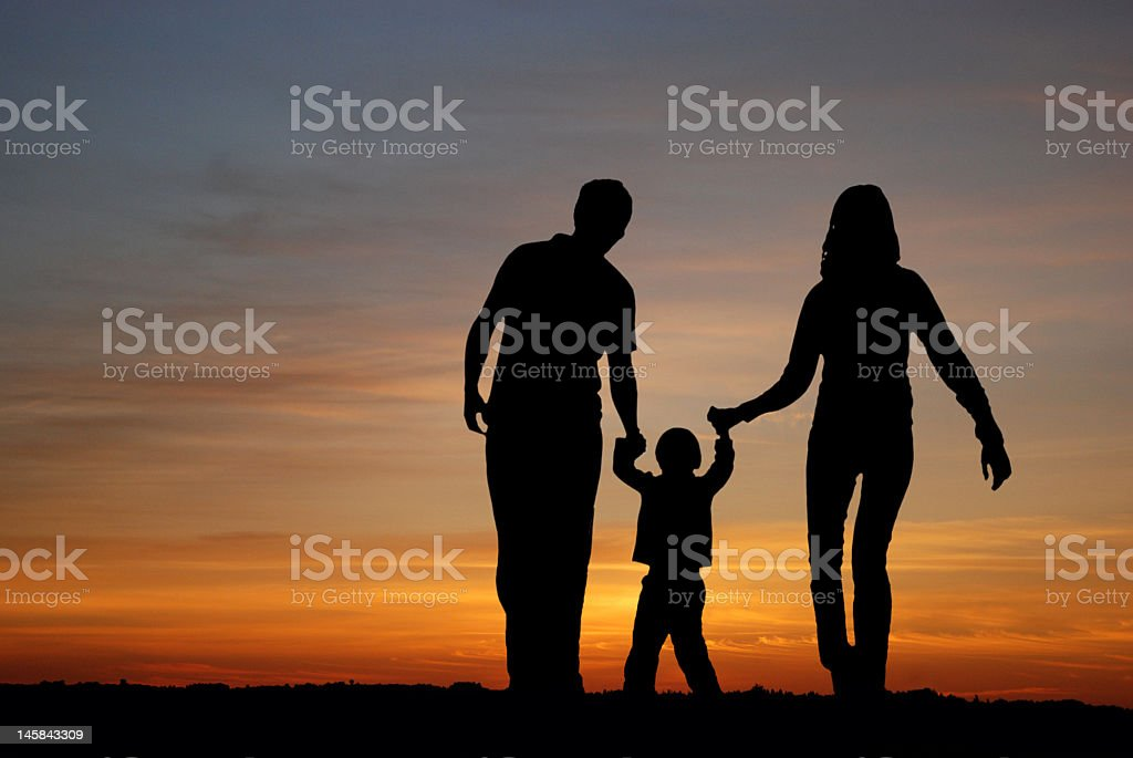 Family walking together at sunset royalty-free stock photo