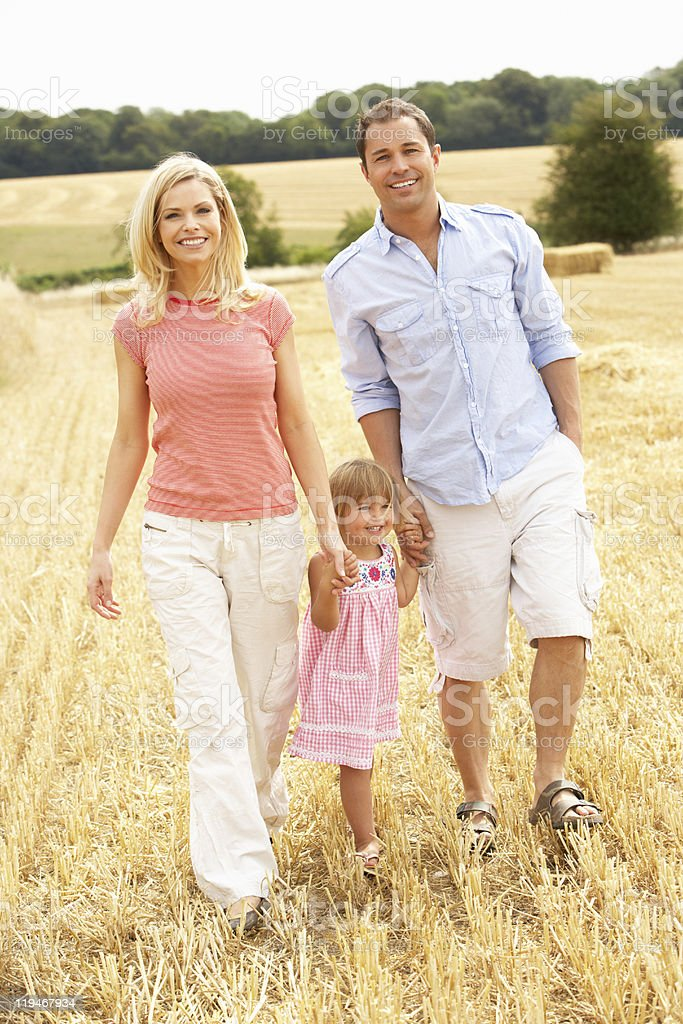 Family Walking Together Through Summer Harvested Field royalty-free stock photo