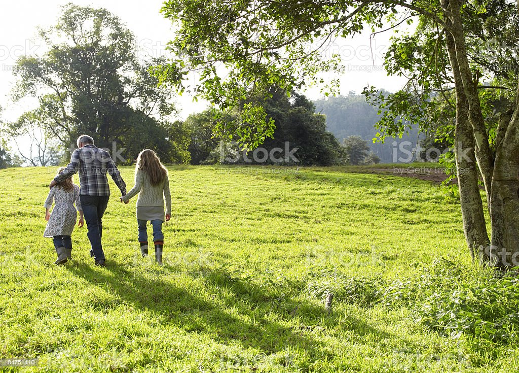 Family walking up a grassy hill together  stock photo