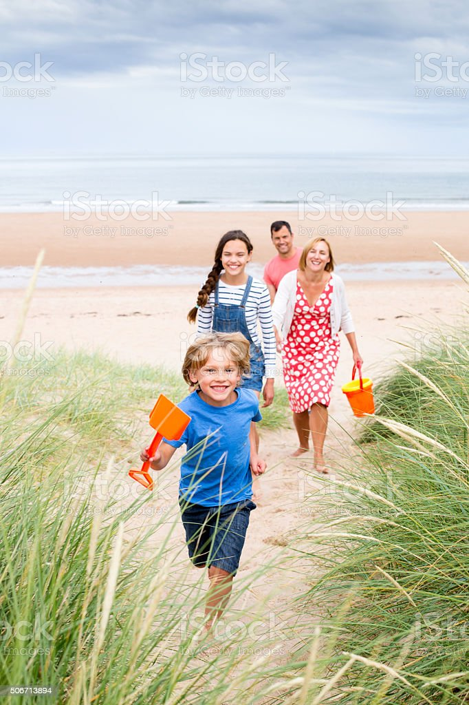 Family walking up the sand dunes stock photo