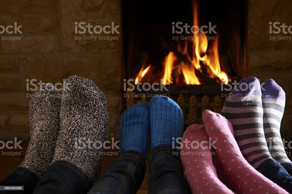 Family Warming Feet By Fire stock photo