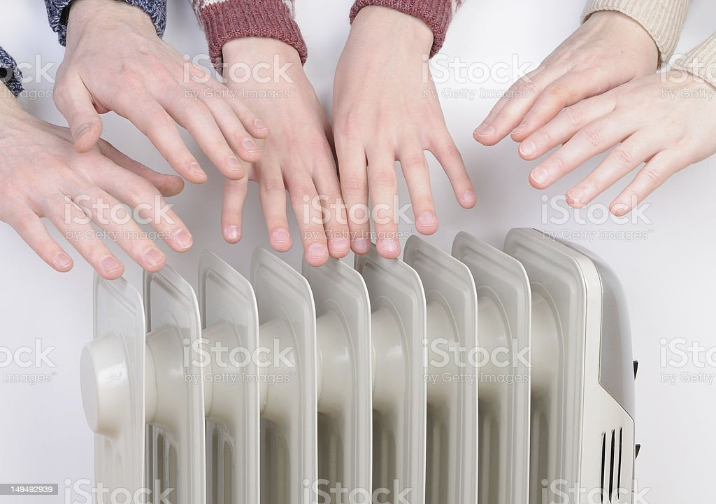 Family warming up hands near an electric heater royalty-free stock photo