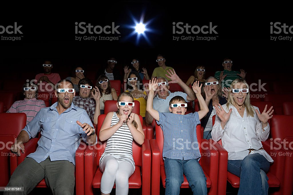 Family watching 3d movie at the movie theater royalty-free stock photo