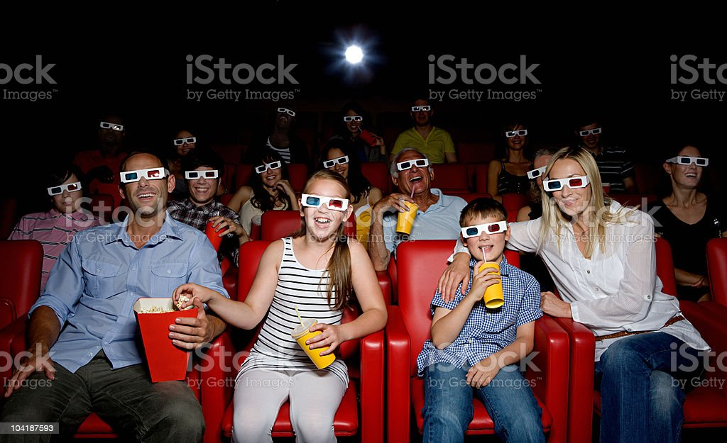Family watching 3d movie at the movie theater stock photo