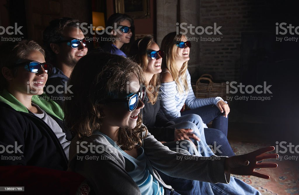 Family watching 3D television on sofa royalty-free stock photo