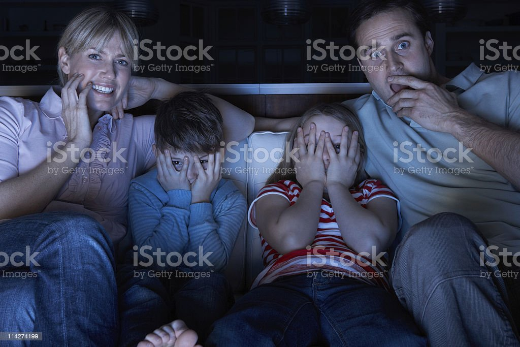 Family Watching Scary TV Programme Sitting On Sofa Together stock photo