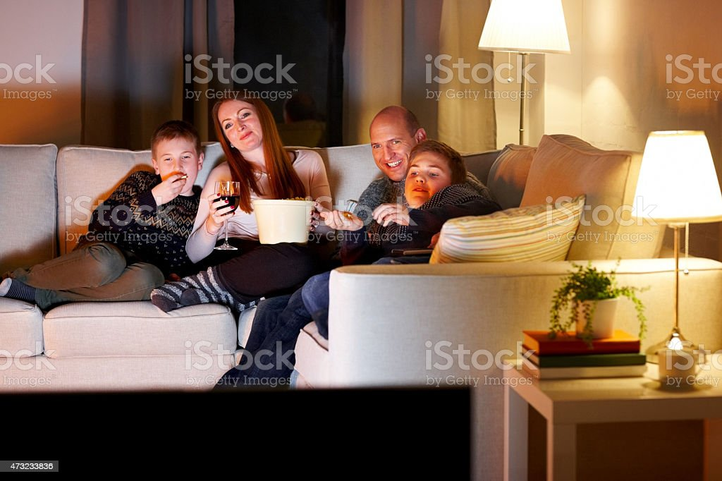 Family watching television at evening stock photo