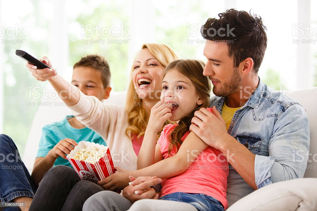 Family watching television in living room stock photo