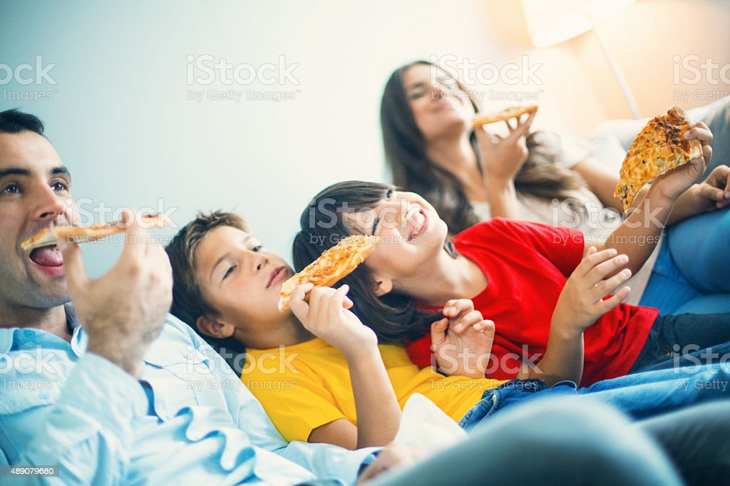 Family watching TV  and eating pizza. stock photo