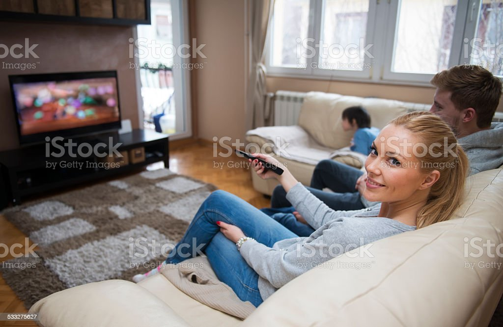 Family watching TV at home stock photo