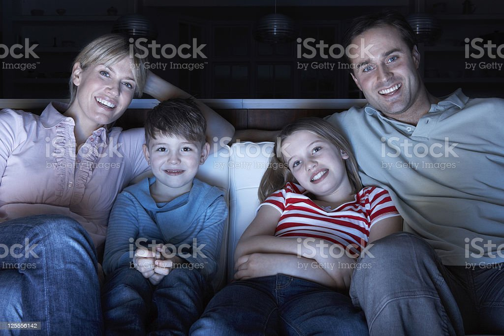 Family Watching TV On Sofa Together stock photo