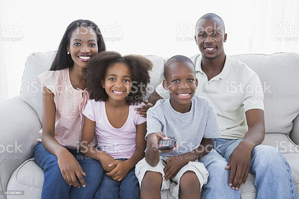 Family watching tv together on couch royalty-free stock photo