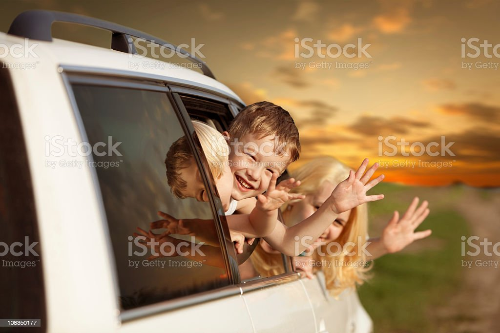 Family waving from car and traveling for a vacation royalty-free stock photo