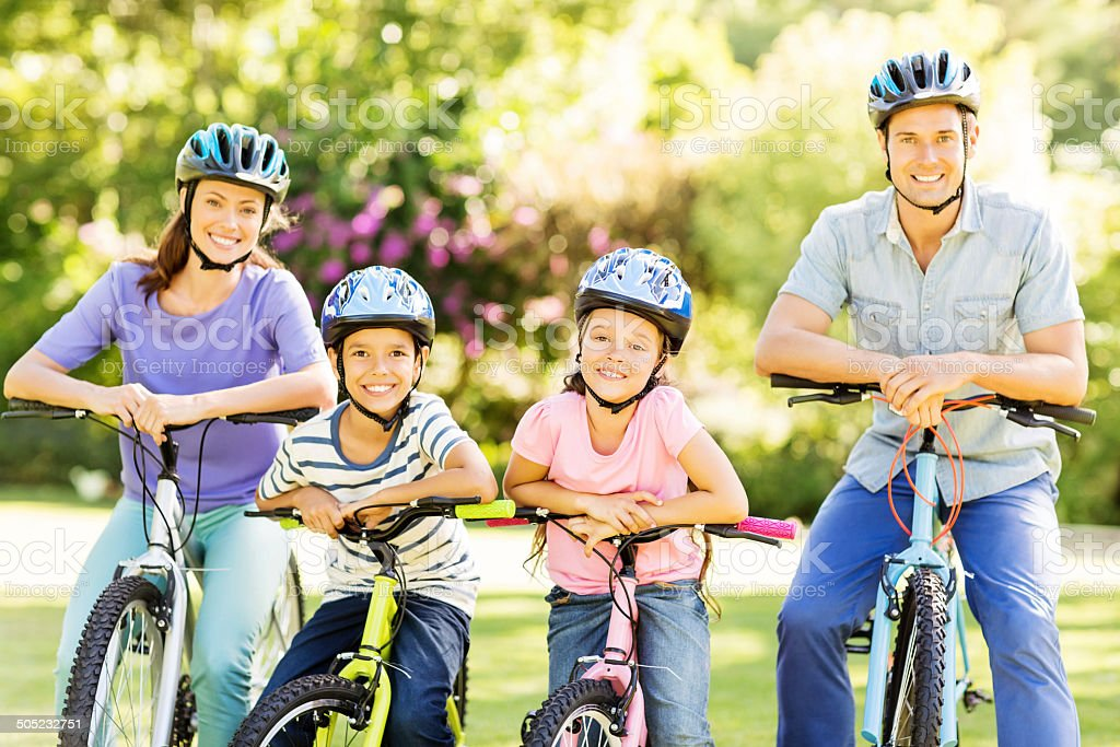 Family Wearing Helmets While Sitting On Bicycles In Park royalty-free stock photo