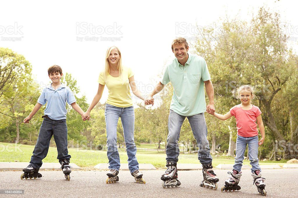 Family Wearing In-Line Skates In Park stock photo