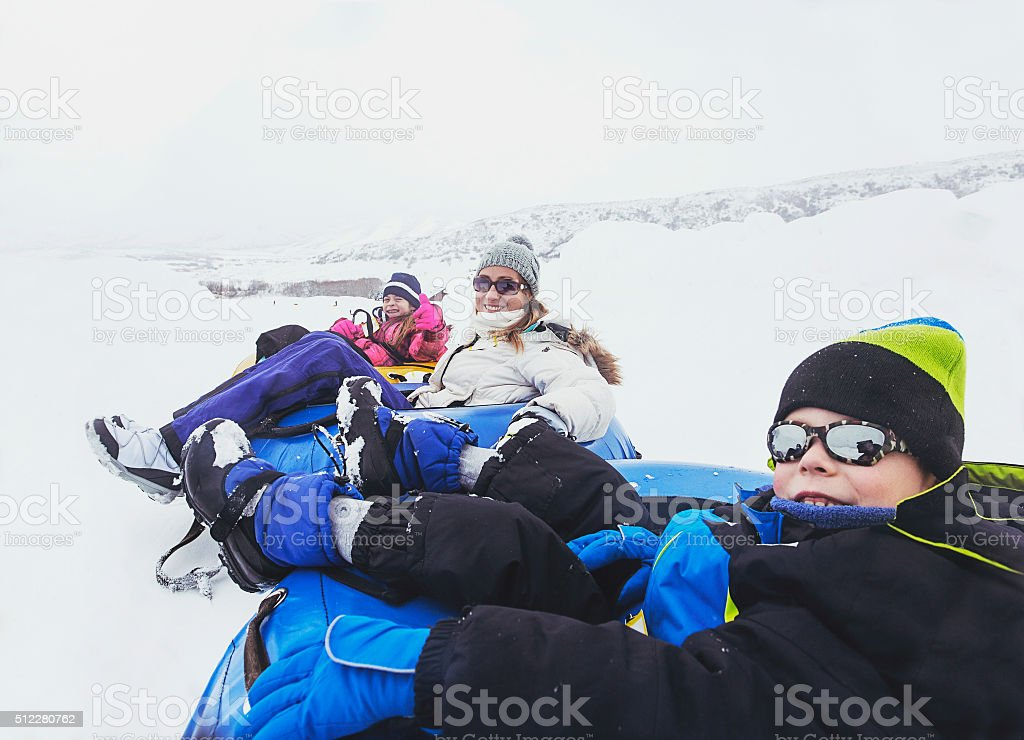 Family winter fun. Sledding and playing in snow stock photo
