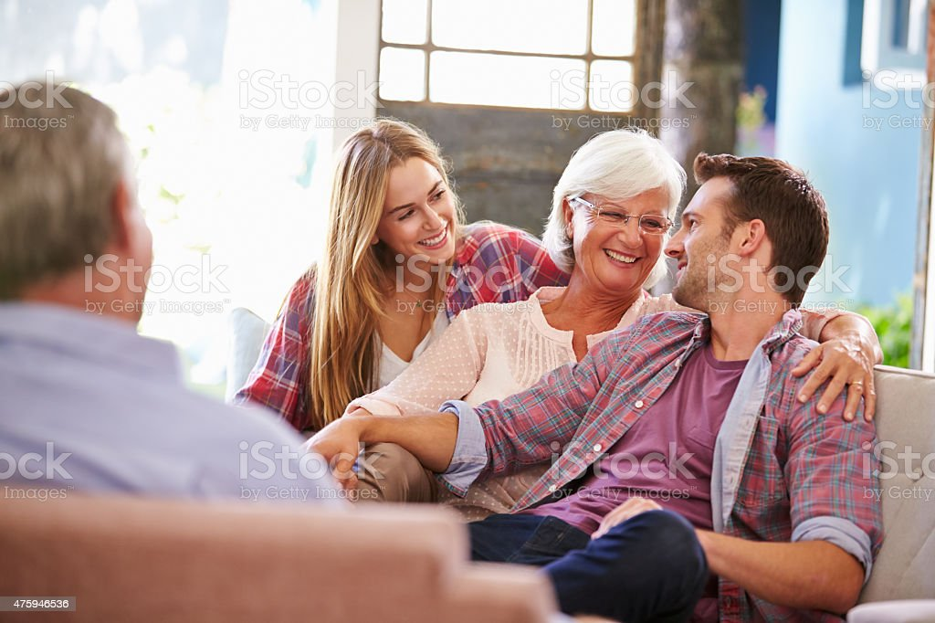 Family With Adult Children Relaxing On Sofa At Home Together stock photo