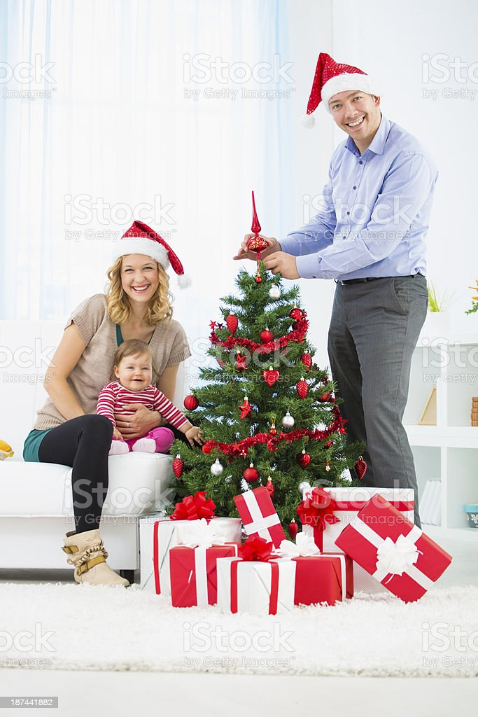 Family with baby decorating Christmas Tree. royalty-free stock photo