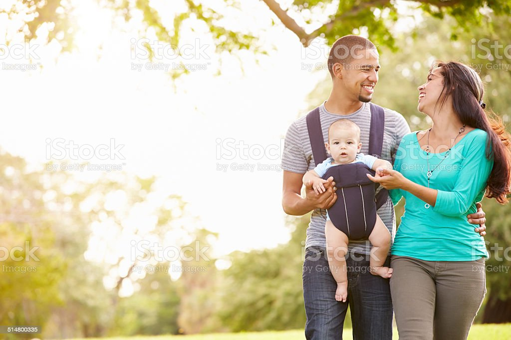 Family With Baby Son In Carrier Walking Through Park stock photo