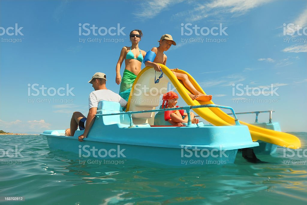 Family with boy and girl on pedal boat in sea stock photo