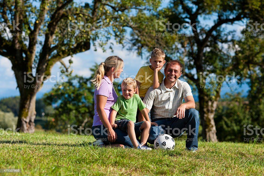 Family with children and football on a meadow royalty-free stock photo