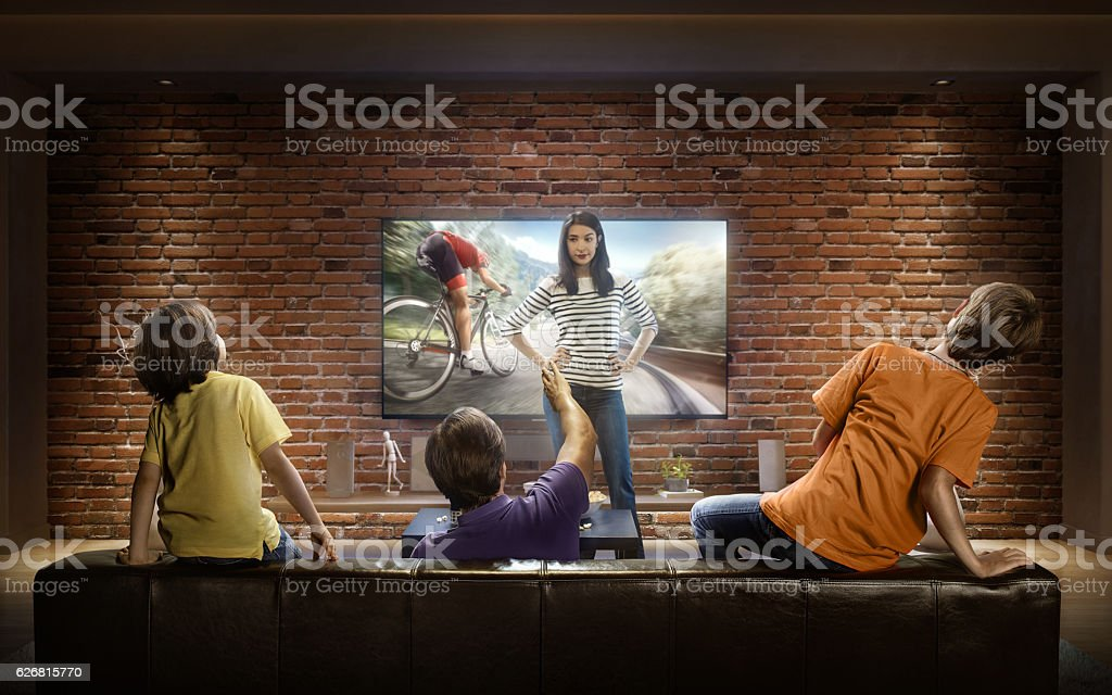 Family with children cheering and watching Cycle race on TV stock photo