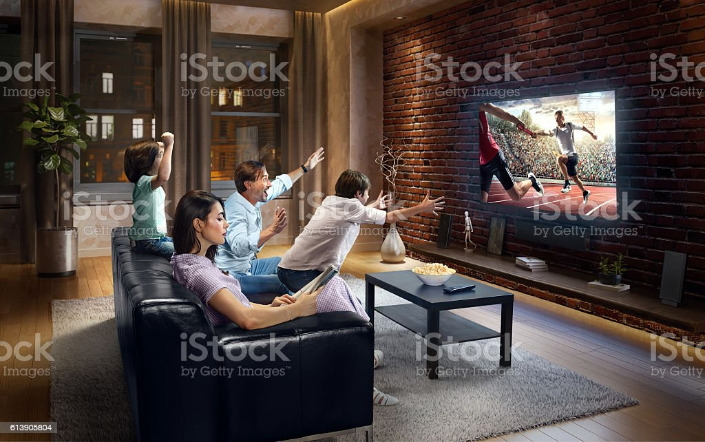 Family with children cheering and watching Relay race on TV stock photo
