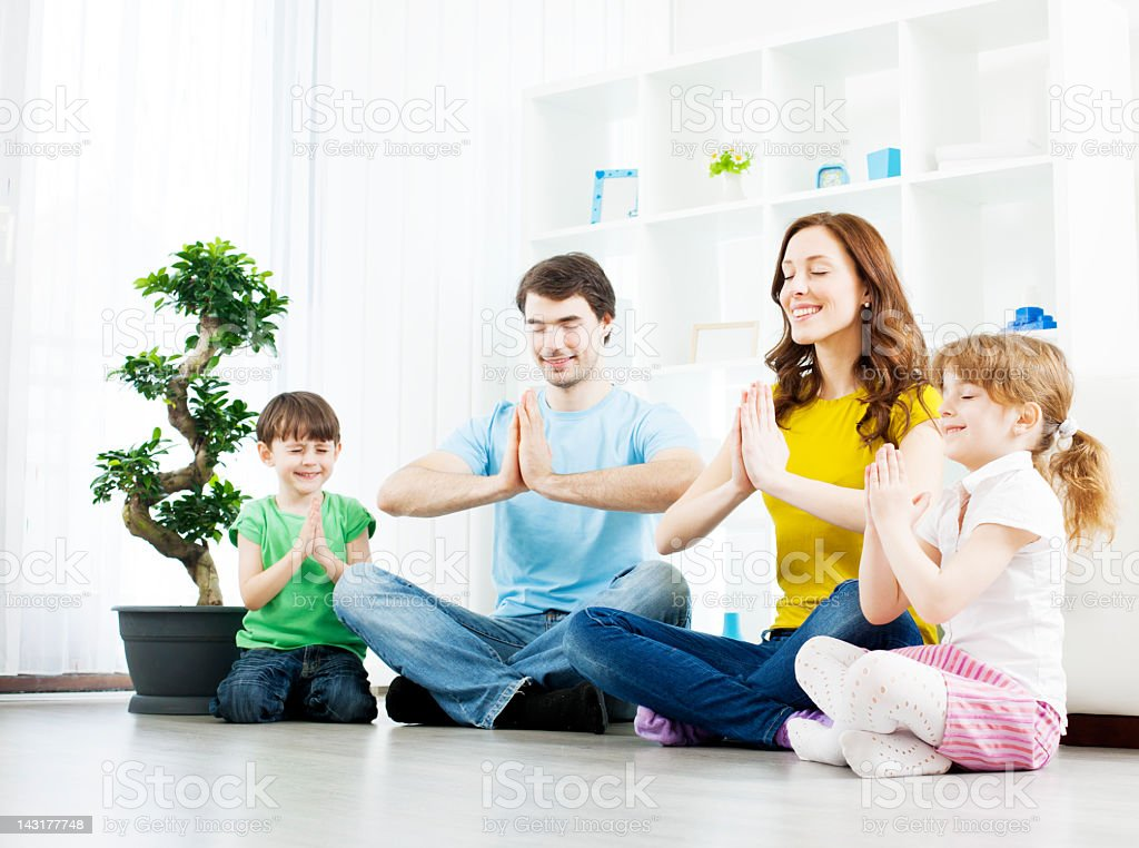 Family with children practicing yoga at home. stock photo