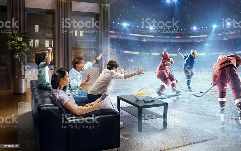 Father and two young children cheering and watching Ice Hockey game...