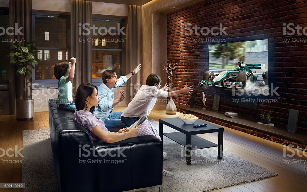Family with children watching Sports Car Race on TV stock photo