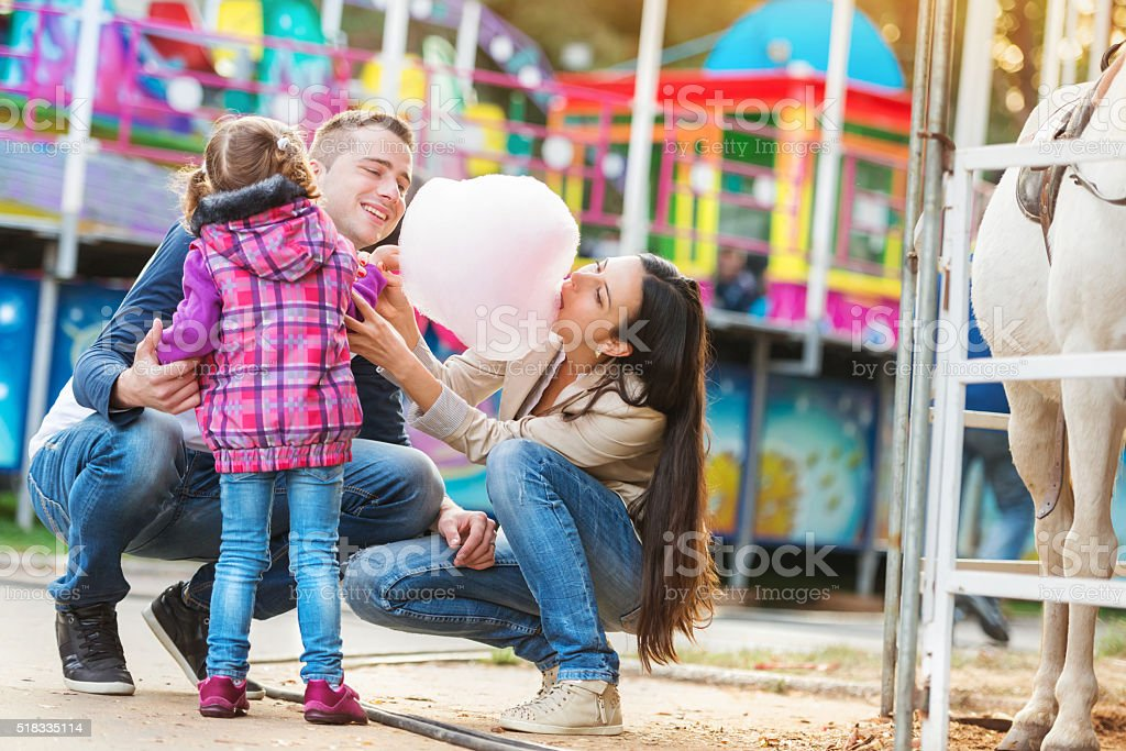 Family with daughter, amusement park, mother eating cotton candy stock photo