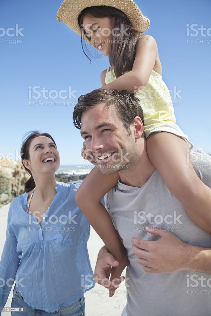 Family with father carrying girl on shoulders royalty-free stock photo