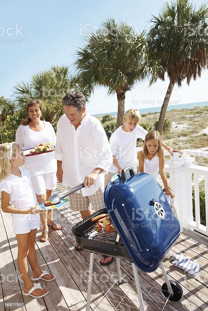 Family with father serving his daughter lunch on a vacation royalty-free stock photo