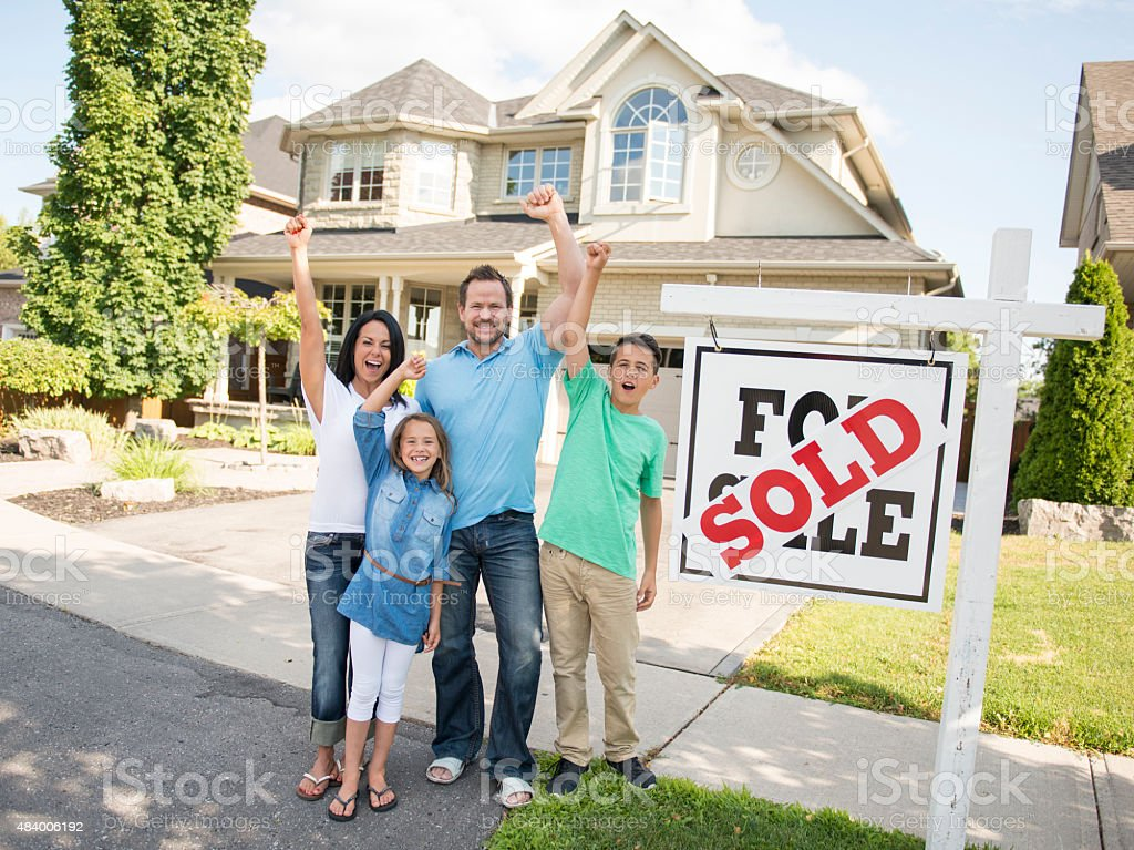 Family with 'For Sale, Sold' real estate sign stock photo