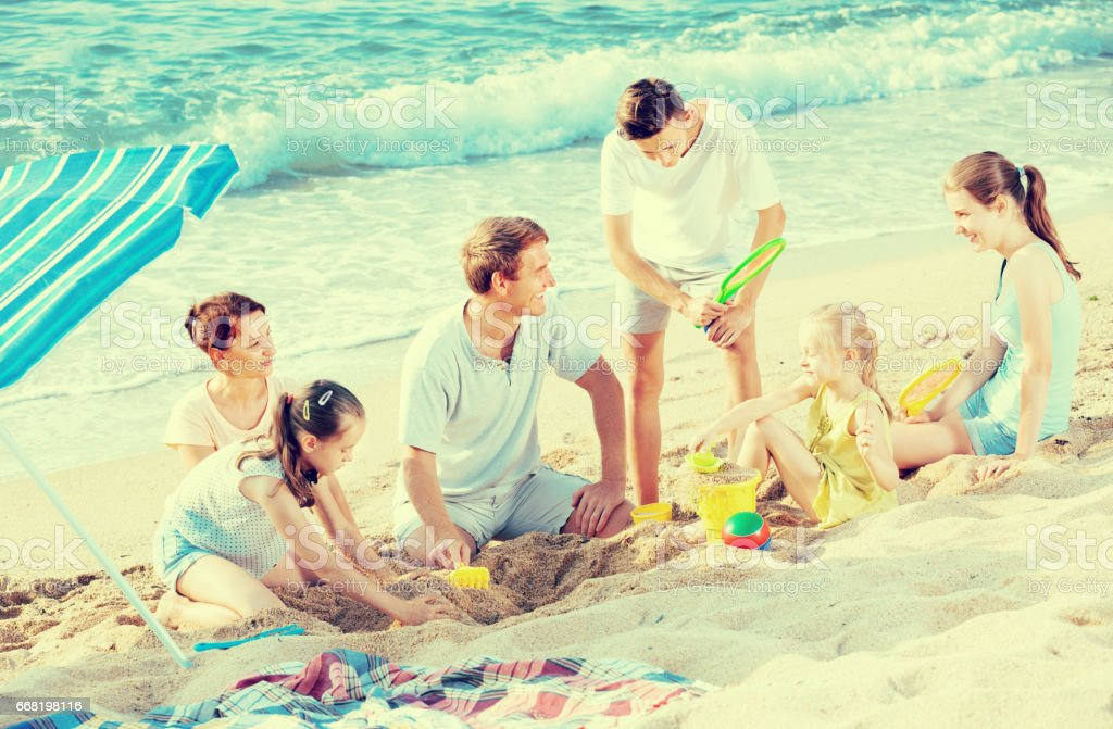 Family with four children playing together on sea beach stock photo