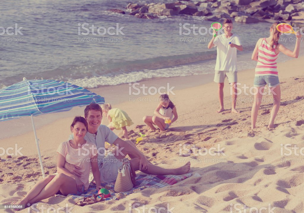 family with four kids relaxing on beach stock photo