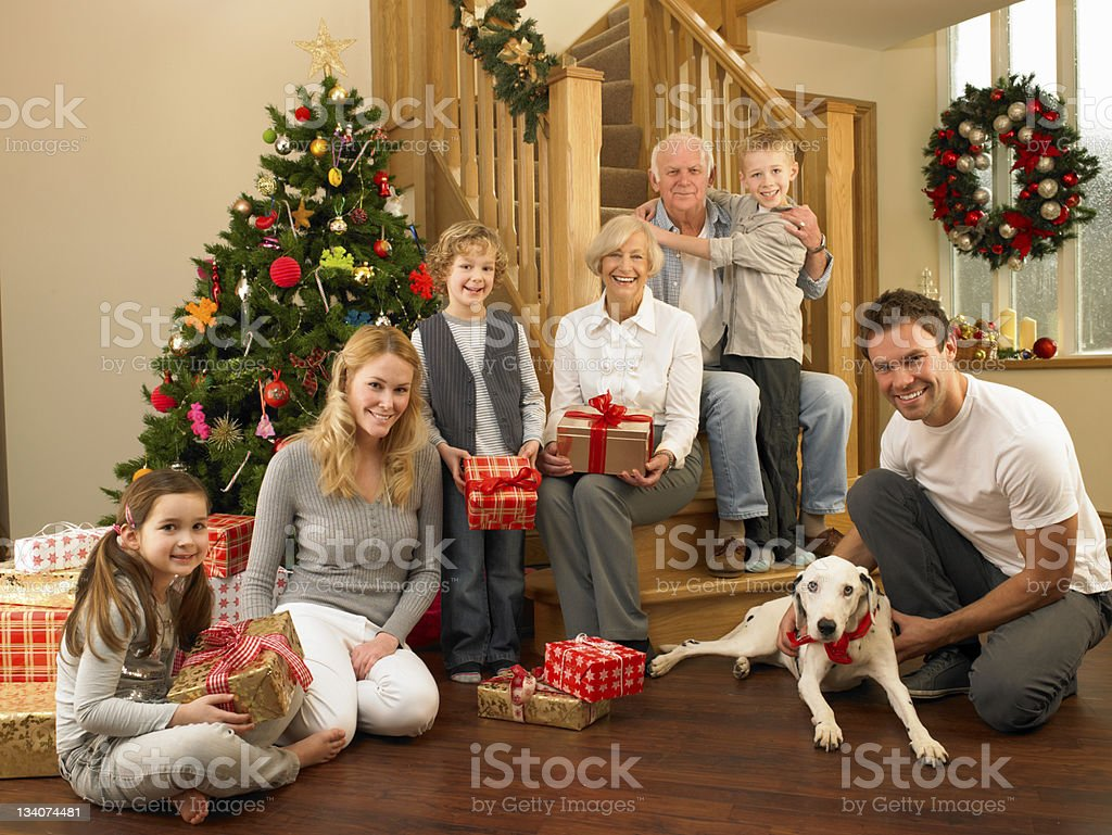 Family with gifts in front of Christmas tree royalty-free stock photo