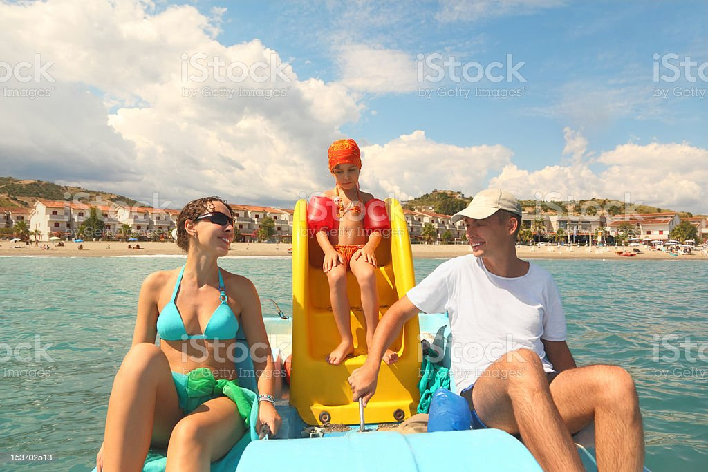 Family with girl on pedal boat in sea stock photo