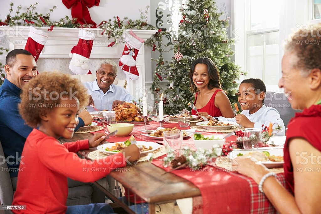 Family With Grandparents Enjoying Christmas Meal At Table stock photo