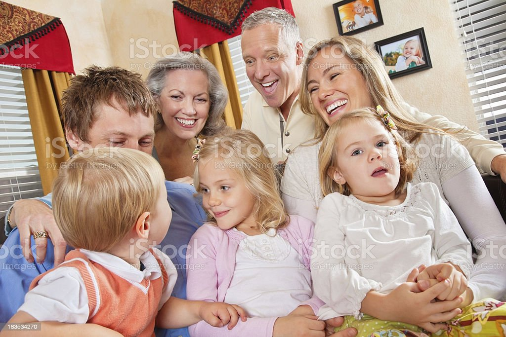 Family With Grandparents Enjoying Time Together in Living Room royalty-free stock photo