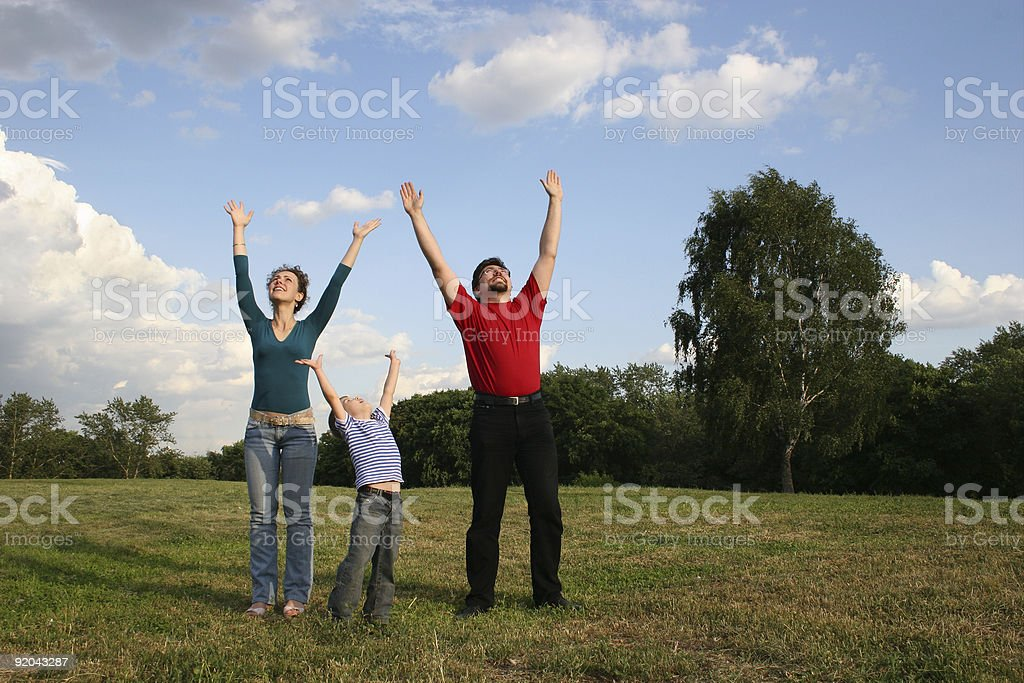 family with hands up on meadow royalty-free stock photo
