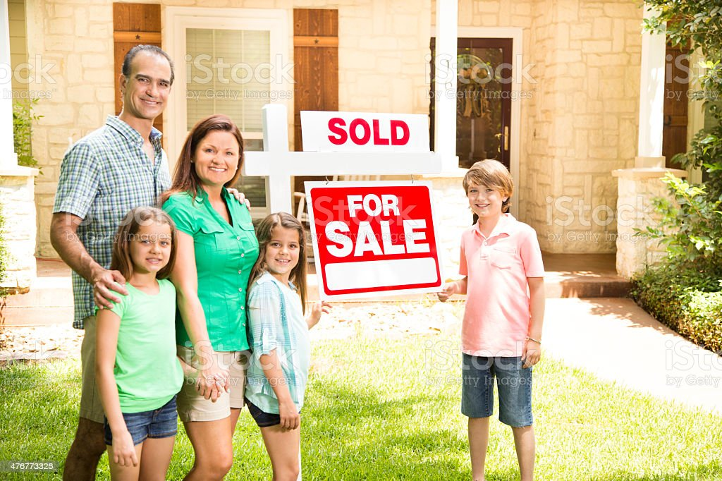 Family with 'house for sale, sold' real estate sign. Summer. stock photo