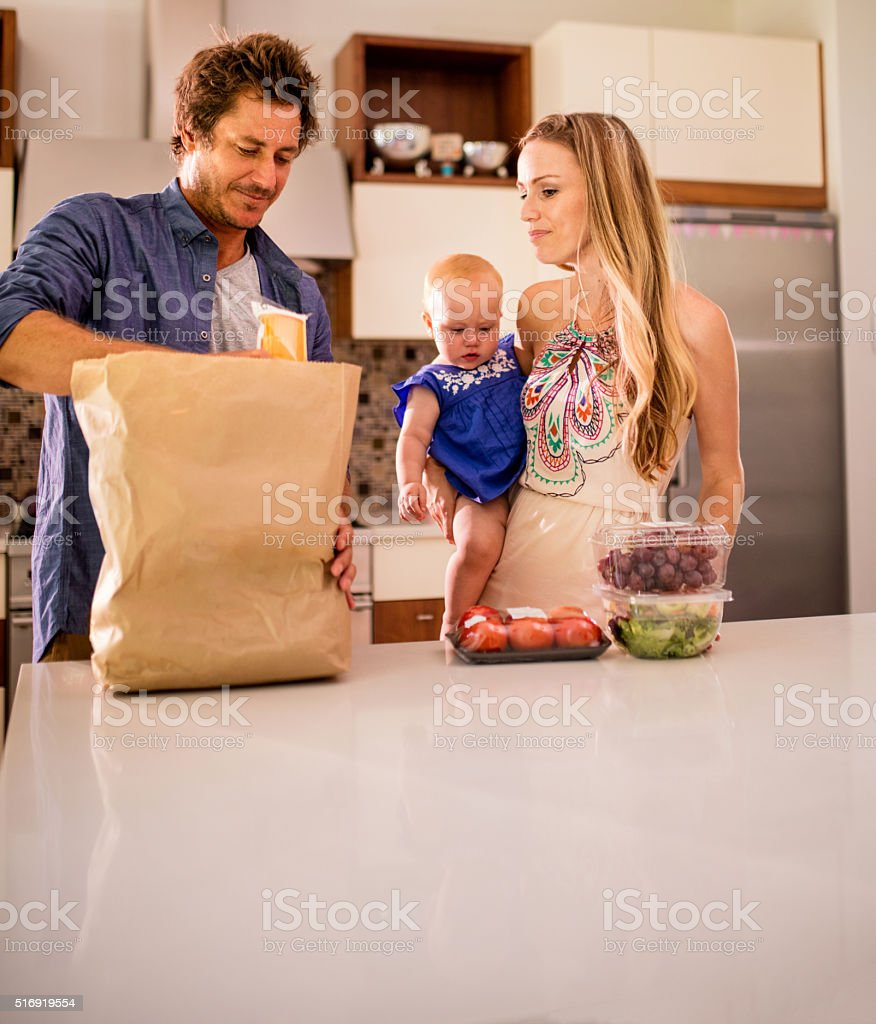 Family with Infant Daughter Unpacking Groceries in Kitchen stock photo