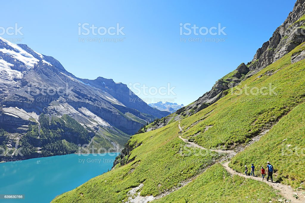 Family with Kids Hiking in the Mountains in summer stock photo