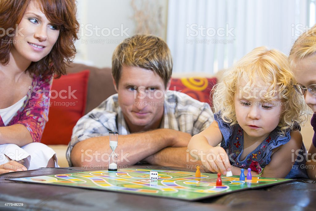 Family with kids is playing a board game stock photo
