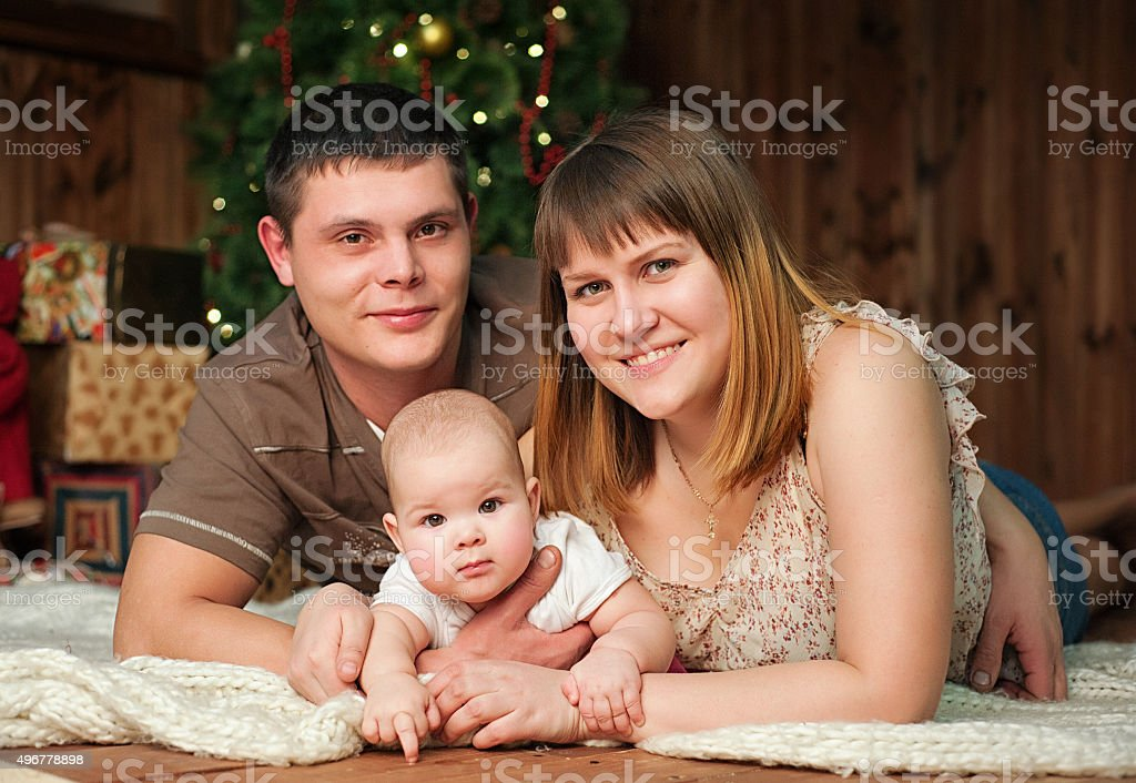 Family with little 7 months girl in front of Christmas stock photo