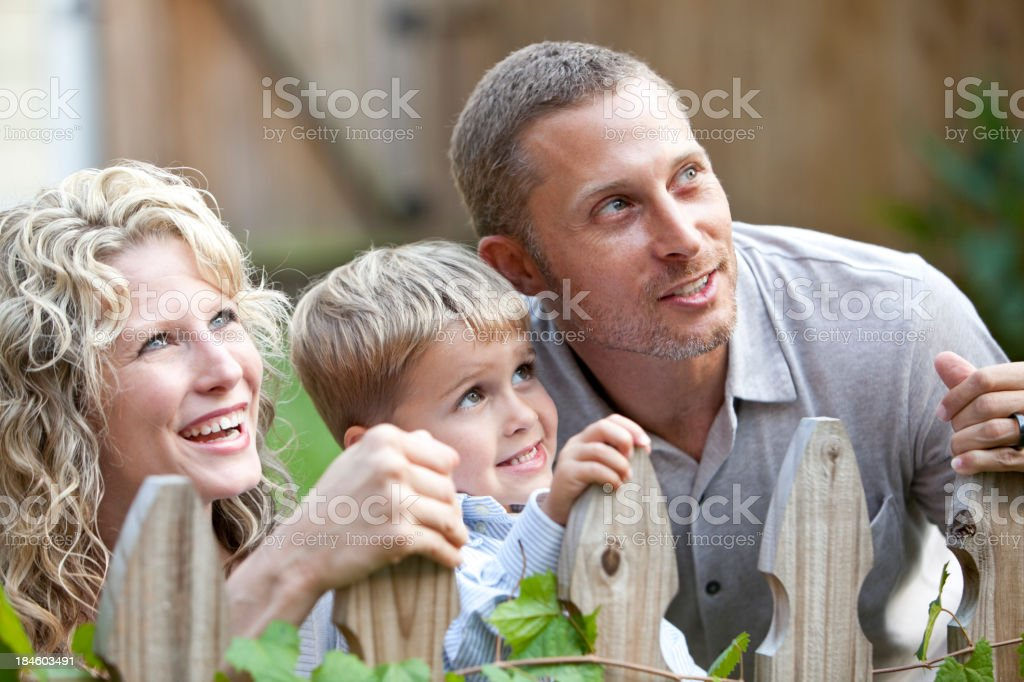 Family with little boy looking over fence royalty-free stock photo