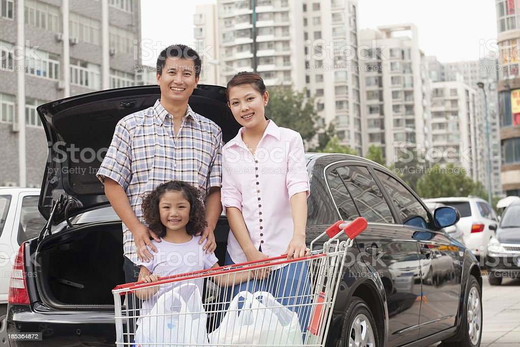 Family with shopping cart standing next to the car royalty-free stock photo
