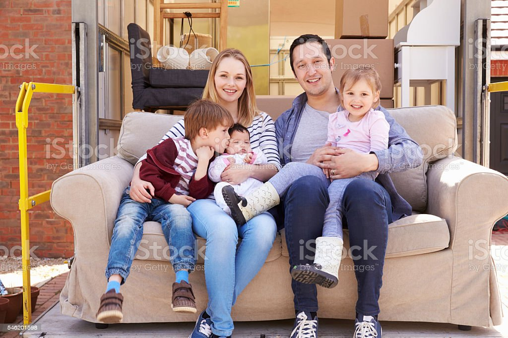 Family With Sofa On Tail Lift Of Removal Truck Moving stock photo